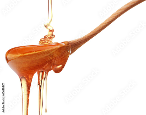 Honey dripping from a wooden honey dipper isolated on white back