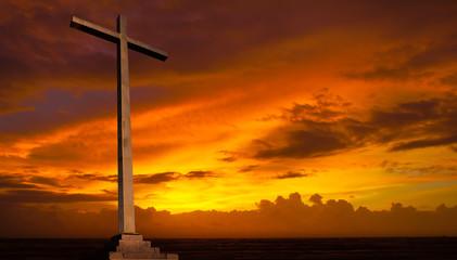 Christian cross on sunset sky. Religion background.