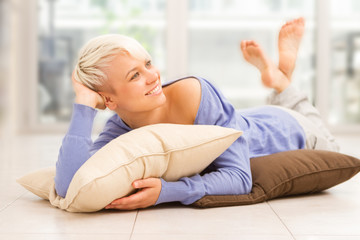 Smiling woman with short hairs laying on a pilow