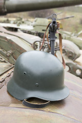 German helmet and Schmeisser submachine gun on the armor of the