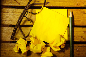 yellow blank paper with crumpled paper with glasses and pencil