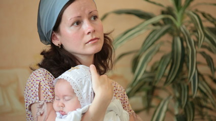 mother with baby in  arms at ceremony of baptism
