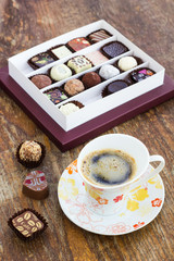 Assorted chocolate candies and cup of coffee on a wooden table