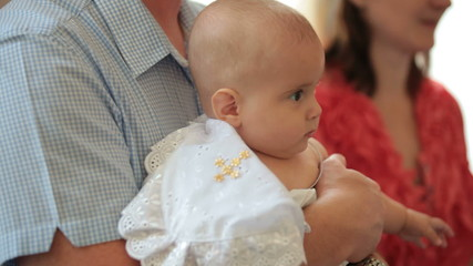 Father holding baby at christening