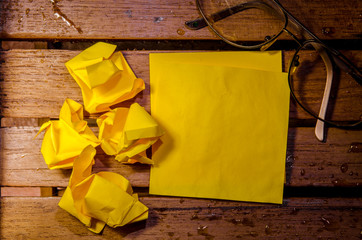 yellow blank paper with crumpled paper with glasses