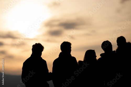 silhouetted group in sunset sky
