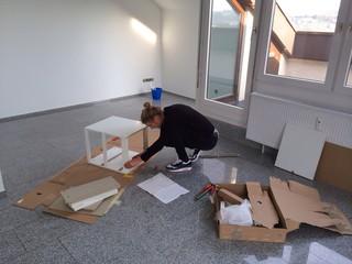 Junge Frau beim Zusammenbau eines Möbelstückes