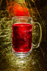 Red drink in glass on gold background