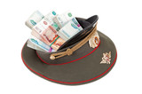Stack of bundled russian ruble banknotes in the officer's cap