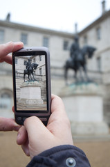 Tourist Holds Up Camera Phone at Nelson's monument