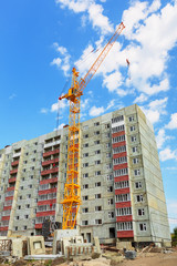 Dwelling house and tower crane on the construction site