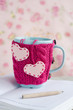 Blue cup in pink sweater with felt hearts standing