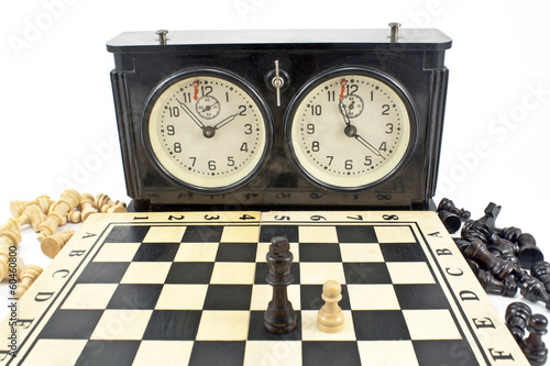 Old chess clock and chessboard  on white