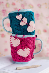 Two blue cups in blue and pink sweater with hearts