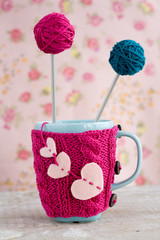 Blue cup in pink sweater with felt hearts with ball of yarn