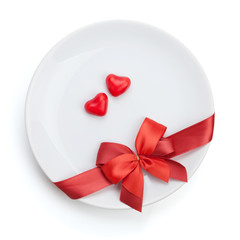 Valentine's Day heart shaped candy over plate with red bow