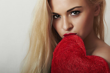 Lovely Beautiful Blond Woman Bites the Red Heart. Love Symbol