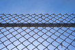 Chain link fence with bar against blue sky