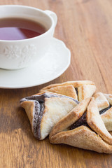 Hamantaschen cookies for Purim with cup of teaon a wooden surfac