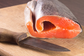 Fresh Salmon with knife on cutting board