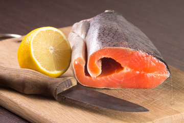 Raw Salmon with Lemon and Knife on Cutting board