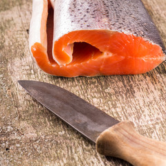 Fresh Salmon with old knife on textured wooden board