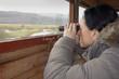 birdwatching, a woman with binoculars in bird hide