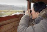 birdwatching, a woman with binoculars in bird hide poster