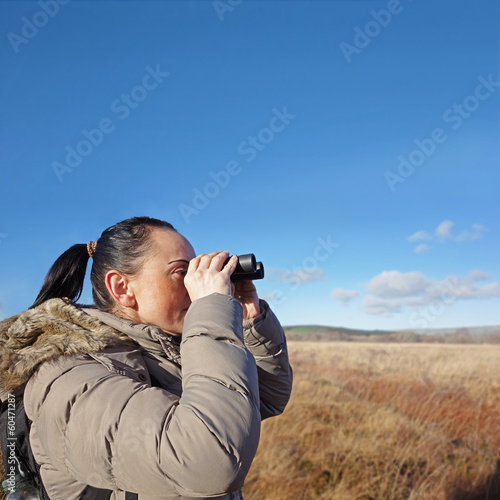 woman with binoculars birdwatching, copy space on blue sky