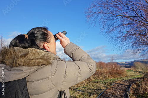 woman with binoculars birdwatching