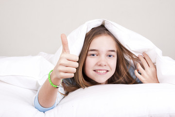 Smiling happy girl in bed under the sheets