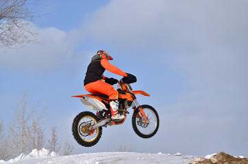 MX rider on the bike jumps from a hill on a snowy highway