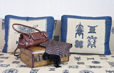 Suitcase, handbag and scarf are on the sofa.