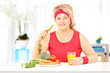 Mature lady at home eating a healthy meal