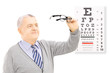 Senior gentleman standing in front of eyesight test holding a pa