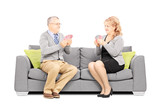 Mature couple playing cards and sitting on sofa