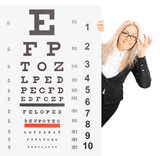Smiling young woman standing behind an eyesight test