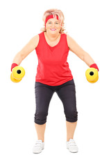 Full length portrait of middle aged woman exercising with dumbbe
