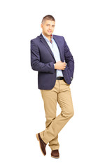 Full length portrait of young fashionable man leaning against a