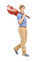 Full length portrait of young man holding an acoustic guitar ove