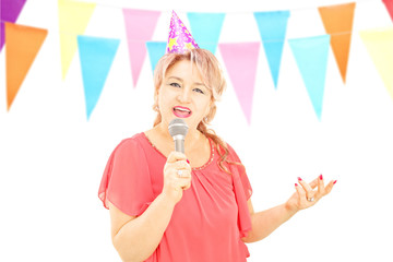Mature lady with party hat singing on microphone at a birthday p