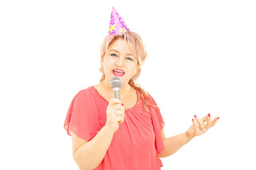 Mature lady with party hat singing on microphone