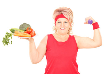 Mature woman holding plate of vegetables and a dumbbell