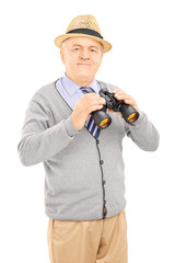 Senior gentleman holding binoculars and looking at camera