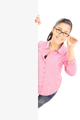 Teenage girl with glasses standing behind blank panel