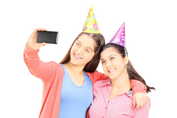 Two teenage girls taking pictures of themselves with cell phone