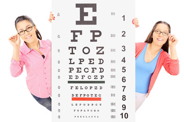 Two teenage girls with glasses standing behind an eyesight test