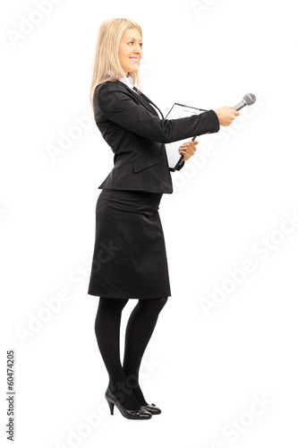 Full length portrait of young female interviewer holding a micro