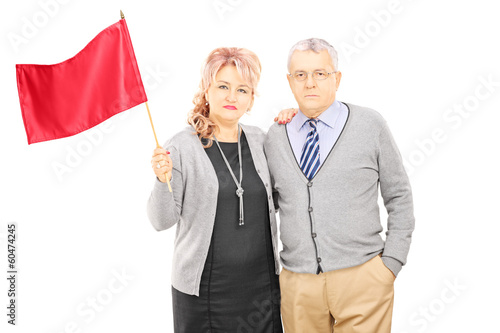 Middle aged couple waving a red flag