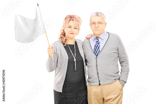 Middle aged couple waving a white flag
